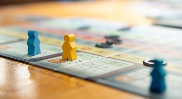 Chiuda sulle figure variopinte della parte della gente sulla tavola con l'amico che gioca nei precedenti