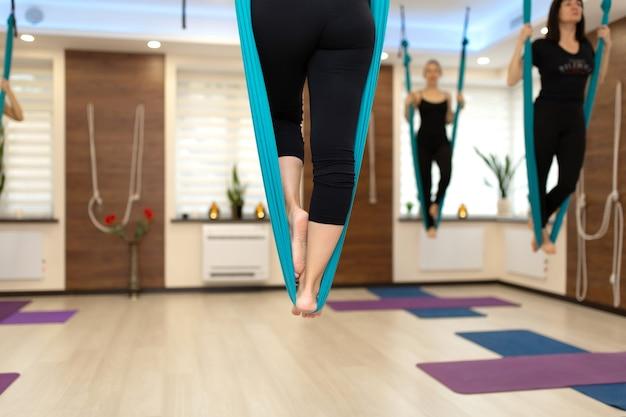 Chiuda sulle gambe della donna che rimangono in amaca che fa l'yoga della mosca che allunga gli esercizi in palestra
