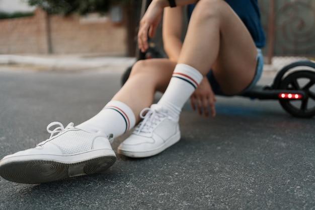 Chiuda sulle gambe della ragazza che si siedono sul suo elettro motorino di estate sulla via