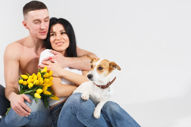 Chiuda sulle giovani coppie del ritratto che si siedono e che abbracciano, tenendo i fiori e il cane gialli