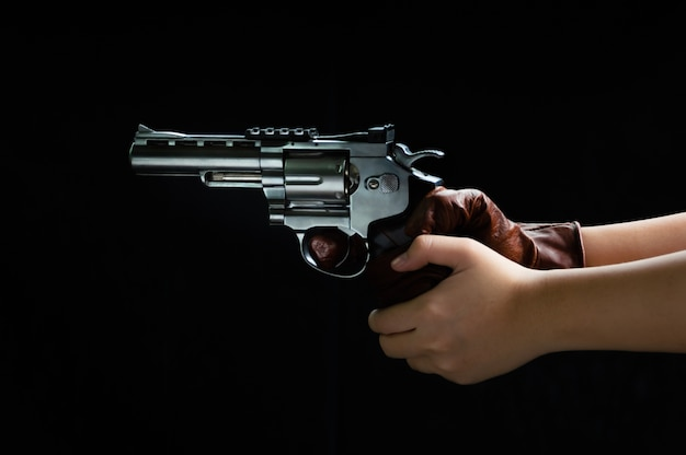 Chiuda sulle immagini della pistola in sua mano pronta a sparare.