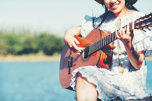 Chiuda sulle immagini delle mani della donna che giocano la chitarra acustica