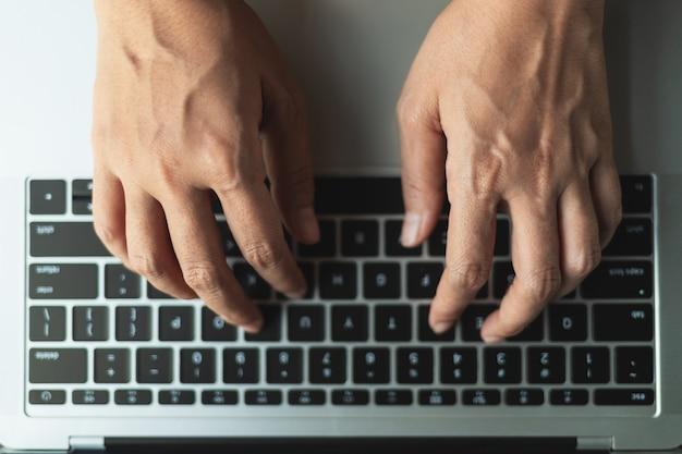 Chiuda sulle mani che digitano un bottone sul computer portatile, vista superiore