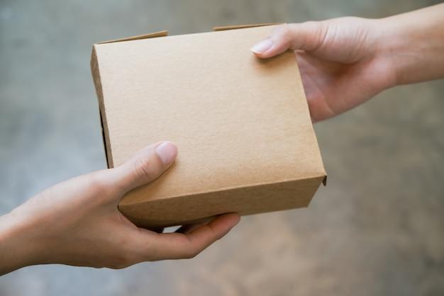 Chiuda sulle mani che passano e ricevono il piccolo pacchetto della scatola marrone.