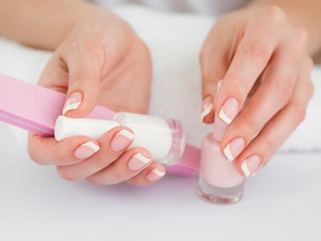 Chiuda sulle mani che tengono gli strumenti del manicure