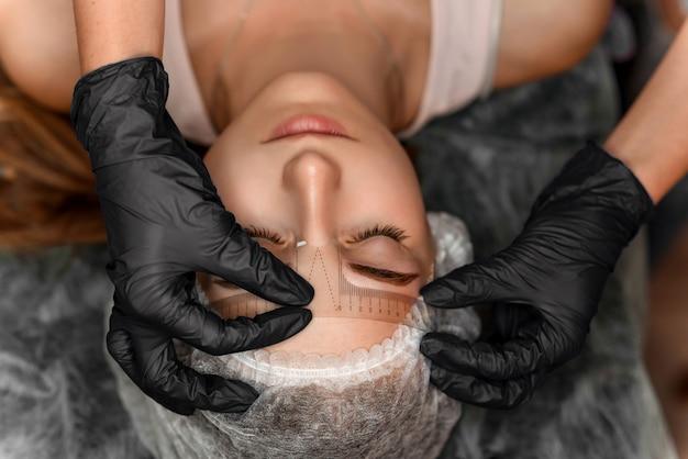 Chiuda sulle mani dell'estetista che fanno il tatuaggio del sopracciglio sul fronte della donna. l'estetista professionista misura la distanza tra le sopracciglia con uno speciale righello per la misurazione delle sopracciglia.