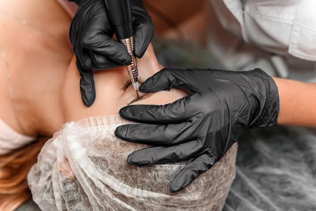 Chiuda sulle mani dell'estetista che fanno il tatuaggio del sopracciglio sul fronte della donna. trucco permanente per sopracciglia nel salone di bellezza. specialista che fa il tatuaggio del sopracciglio per il viso femminile. trattamento di cosmetologia