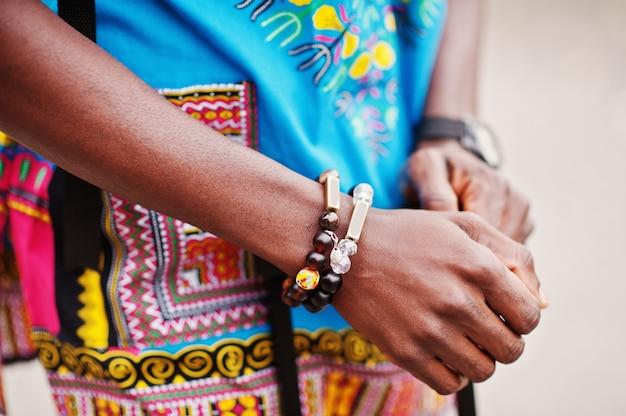 Chiuda sulle mani dell'uomo africano in camicia tradizionale dell'africa con i braccialetti.