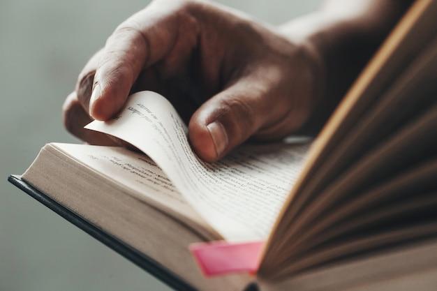Chiuda sulle mani dell'uomo. giovane uomo che apre e che legge un libro,