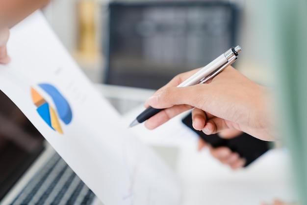 Chiuda sulle mani della donna che indicano la penna alla carta del grafico di dati di gestione per la spiegazione di informazioni commerciali