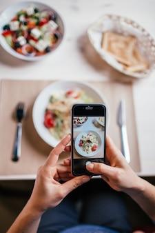 Chiuda sulle mani della donna che prendono la foto di insalata fresca sulla tavola con il suo telefono.