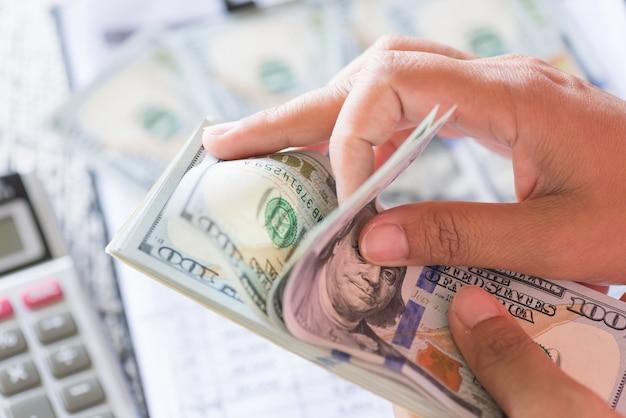 Chiuda sulle mani della donna che tengono e che contano la banca delle banconote dei dollari dell'america