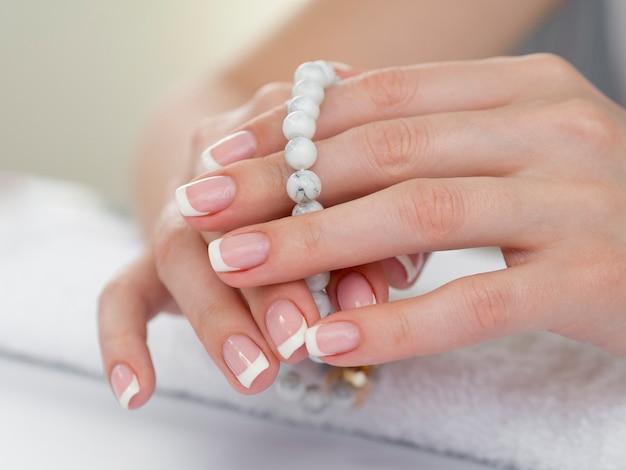 Chiuda sulle mani della donna che tengono le perle