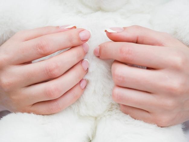 Chiuda sulle mani della donna con tessuto lanuginoso