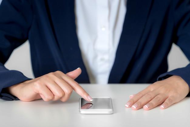 Chiuda sulle mani della donna di affari facendo uso dello smartphone sulla visualizzazione di schermo in bianco