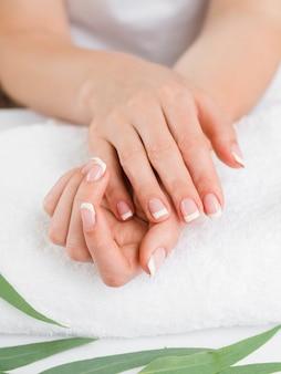 Chiuda sulle mani della donna sull'asciugamano molle