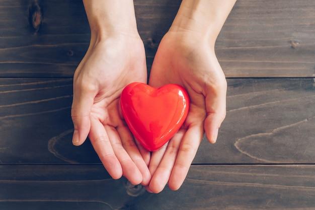 Chiuda sulle mani femminili che danno il cuore rosso su fondo di legno