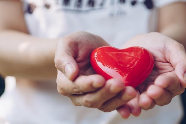 Chiuda sulle mani femminili che danno il cuore rosso sulle mani