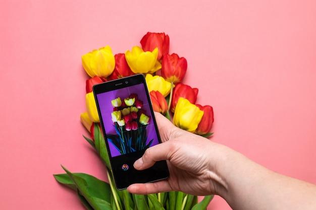 Chiuda sulle mani femminili che prendono la foto di bei fiori con lo smartphone