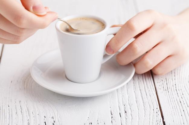 Chiuda sulle mani femminili con la tazza di caffè sul tavolo. primo piano della pausa caffè