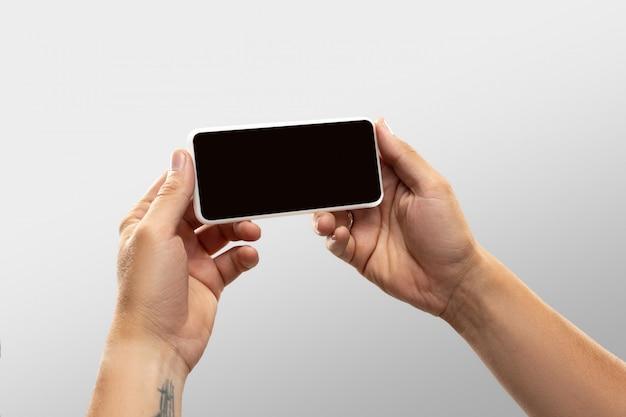 Chiuda sulle mani maschii che tengono il telefono con lo schermo in bianco durante la sorveglianza online delle partite e dei campionati di sport popolari intorno al mondo.