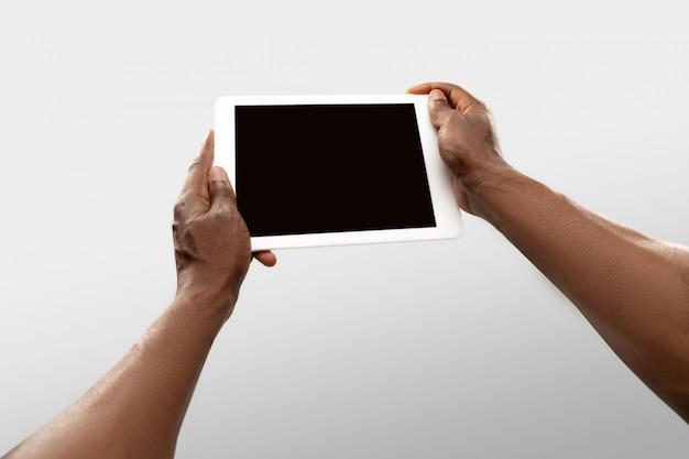 Chiuda sulle mani maschii che tengono la compressa con lo schermo in bianco durante la sorveglianza online delle partite e dei campionati di sport popolari intorno al mondo.