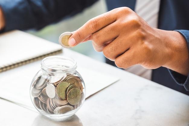 Chiuda sulle monete della tenuta dell'uomo d'affari della mano che mettono in vetro. concetto dei soldi di risparmio, concetto dei soldi di finanza, concetto di investimento