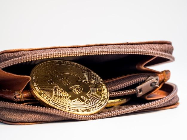 Chiuda sulle monete di oro del bitcoin con il portafoglio sul bianco.