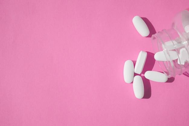 Chiuda sulle pillole bianche con la bottiglia su fondo rosa.