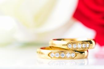 Chiuda sulle rose rosse e sugli anelli di oro su bianco