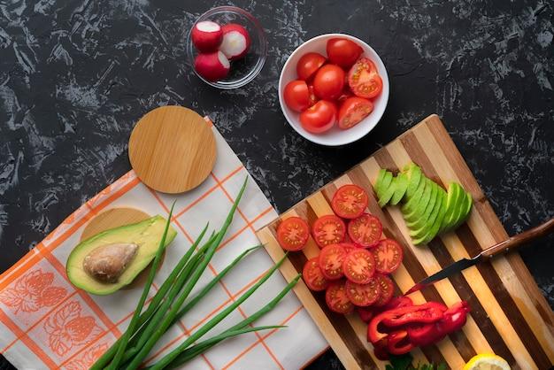 Chiuda sulle verdure affettate di disposizione piana organica fresca sul tagliere, sul pomodoro, sull'avocado, sui peperoni