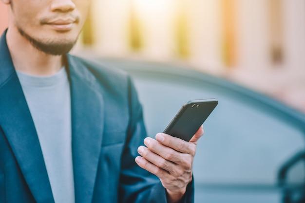 Chiuda sullo smart phone mobile della tenuta dell'uomo