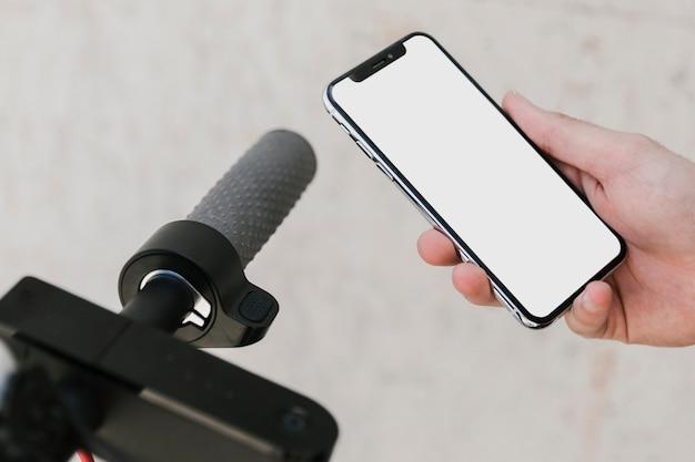 Chiuda sullo smartphone del modello con la maniglia dello e-motorino