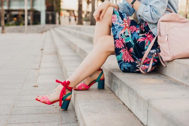 Chiudere i dettagli delle gambe in sandali rosa di donna seduta sulle scale in una strada cittadina in elegante gonna stampata con zaino in pelle, tendenza stile estivo