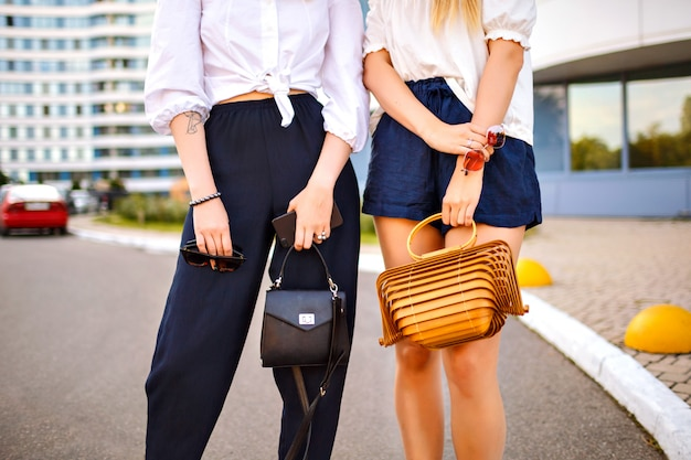 Chiudere i dettagli di moda di due donne alla moda in posa per strada, indossando abiti eleganti abbinati a colori, concentrarsi su borse e accessori di lusso, primavera estiva.