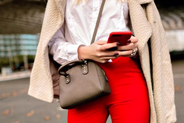 Chiudere i dettagli di moda, donna d'affari, ha toccato qualcosa sul suo telefono, sfondo urbano della città autunnale, abito luminoso e cappotto di cashmere, pronto per la conferenza.