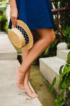 Chiudere i dettagli gamba magra della giovane donna sottile sexy in vestito blu che tiene il cappello di paglia camminare a piedi nudi in hotel villa spa tropicale in vacanza in abito stile estivo