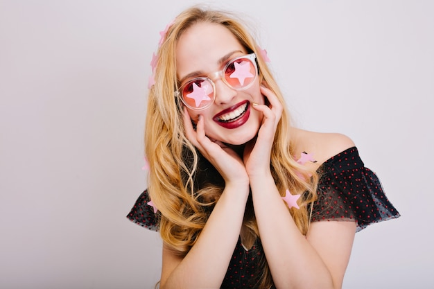 Chiudere il ritratto della splendida ragazza con bei capelli ricci biondi, denti perfetti, divertirsi, servizio fotografico di festa, sorridente. indossare occhiali rosa fantasia, bel vestito.