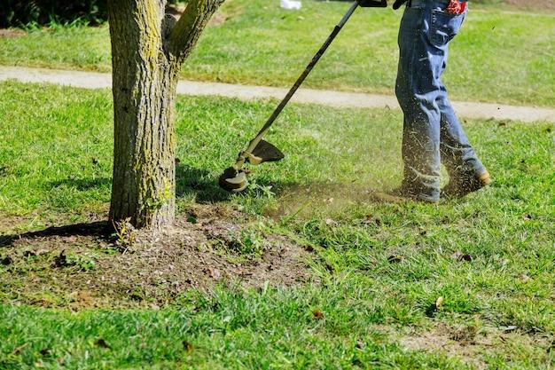 Chiudere la mano dell'uomo utilizzando il tagliaerba tosaerba taglio erba sul fuoco selettivo verde a portata di mano