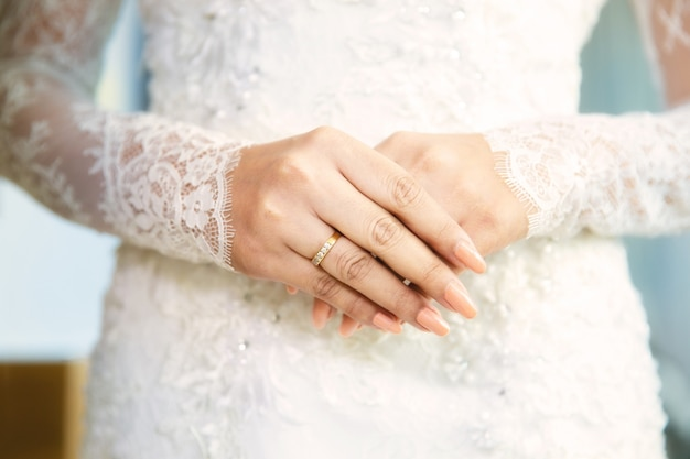 Chiudere le mani con anello di fidanzamento con diamante sul dito della sposa in abito bianco o abito da sposa. anello di diamante della donna elegante sul dito della sposa nella cerimonia di nozze.