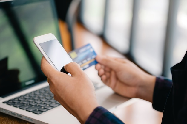 Chiudere le mani effettuando il pagamento online. mani dell'uomo in possesso di una carta di credito e utilizzo di smart phone per lo shopping online