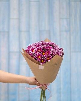 Chiudere sulla mano che tiene il mazzo di fiori