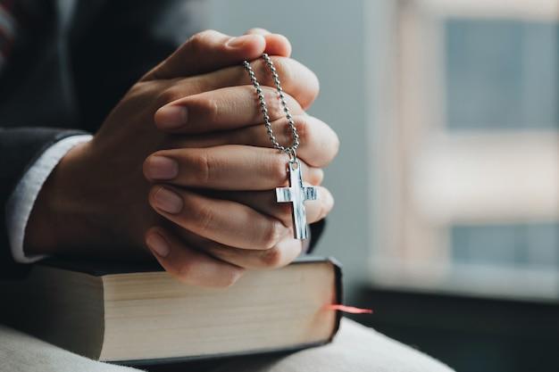 Chiudi le mani. uomini d'affari che tengono la croce di gesù e pregano le mani e la sacra bibbia di fronte