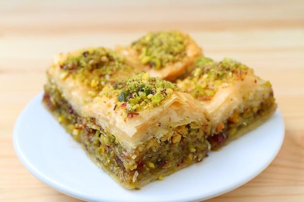 Chiuso su di baklava con pistacchi servita sul piatto bianco, sfondo sfocato