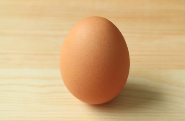 Chiuso un uovo di gallina crudo isolato sul tavolo di legno