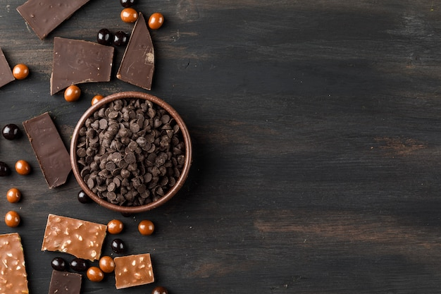 Choco cade con chocoballs e barrette di cioccolato in una ciotola di argilla sul tavolo di legno
