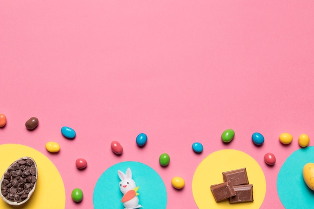 Choco chips; statua di coniglio; pezzi di cioccolato e caramelle colorate su sfondo rosa con spazio per il testo