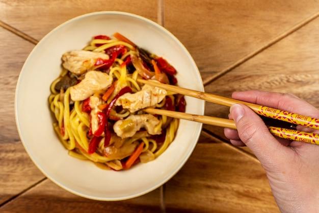 Chow mein di pollo e bacchette sul tavolo di legno