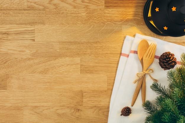 Christmastable con la vista superiore di legno del cucchiaio e della forchetta e della lanterna. copia spazio.