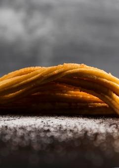 Churros deliziosi di vista frontale del primo piano su una coperta di zucchero